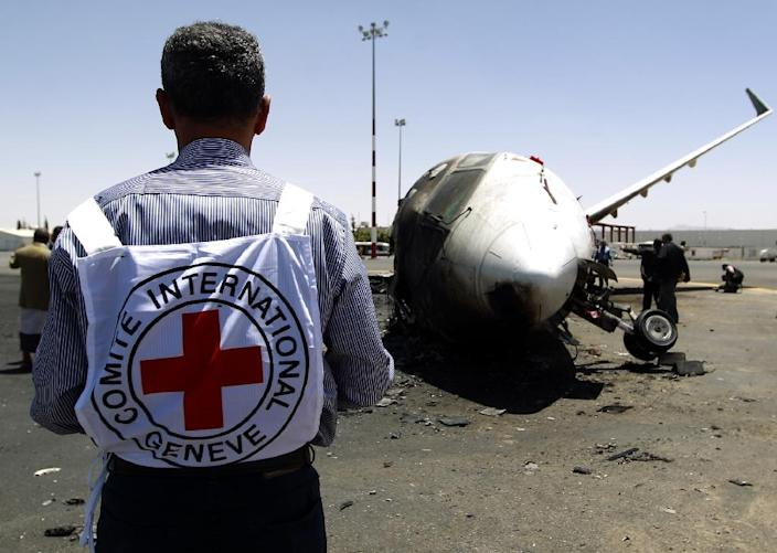 A member of the International Committee of the Red Cross stands in front of a destroyed Felix Airways plane after it was hit in an air strike at the airport in Yemen's capital Sanaa on April 29, 2015 (AFP Photo/Mohammed Huwais)