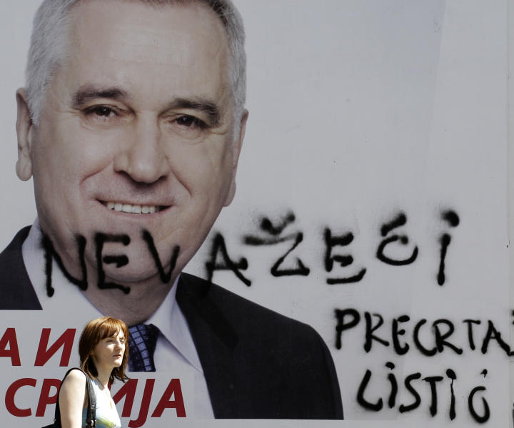 "A woman passes by billboard showing presidential candidate Tomislav Nikolic, leader of the opposition Serbian Progressive Party (SNS), vandalized with paint reading: ""Invalid"" and ""Cross the ballot"", in Belgrade, Serbia, Tuesday, May 1, 2012. The sebian presidential election is on May 6. (AP Photo/Darko Vojinovic)"