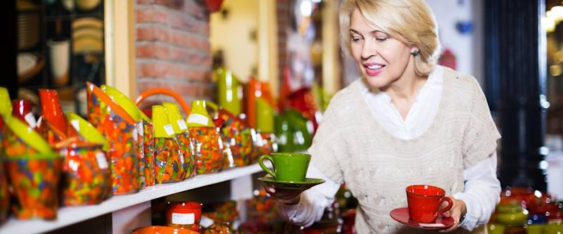 Blonde woman chooses ceramic ware in the cookware section at hypermarket