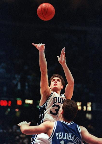 "FILE - In this March 28, 1992, file photo, Duke's Christian Laettner takes the winning shot in overtime over Kentucky's Deron Feldhaus for a 104-103 victory in the East Regional Final NCAA college basketball game in Philadelphia. For the first time since Laettner's improbable buzzer-beater, head coaches Mike Krzyzewski and Rick Pitino are meeting in the regional finals of the NCAA tournament. Pitino is across the state in Louisville these days, but that doesn't lessen the drama of their long-awaited ""rematch."" (AP Photo/Charles Arbogast, File)"