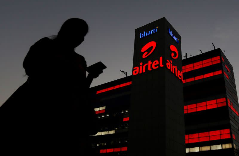 A girl checks her mobile phone as she walks past the Bharti Airtel office building in Gurugram