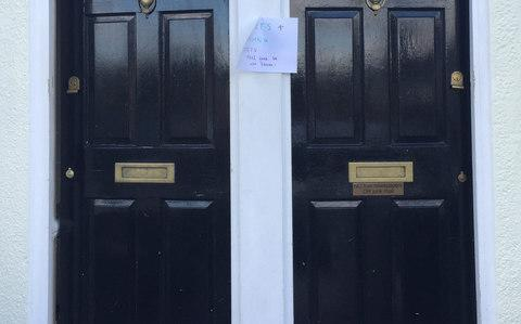 A note pinned outside two houses close to Parsons Green station in London welcoming strangers inside - Credit: Tess De La Mare /PA