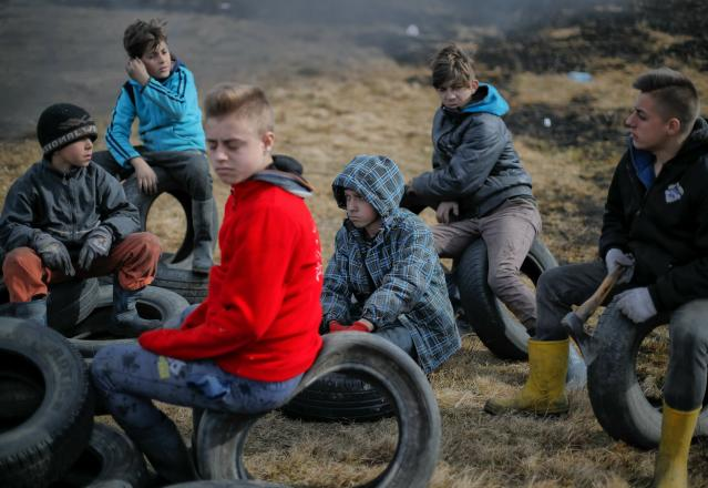 In this photo taken on Sunday, March 10, 2019, a children sit on tires during a ritual marking the upcoming Clean Monday, the beginning of the Great Lent, 40 days ahead of Orthodox Easter, on the hills surrounding the village of Poplaca, in central Romania's Transylvania region. Romanian villagers burn piles of used tires then spin them in the Transylvanian hills in a ritual they believe will ward off evil spirits as they begin a period of 40 days of abstention, when Orthodox Christians cut out meat, fish, eggs, and dairy. (AP Photo/Vadim Ghirda)