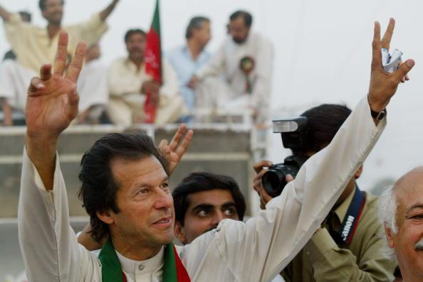 SHADI KHAL, PAKISTAN - OCTOBER 8:  Imran Khan, cricket captain turned politician and chairman of the Dhirir Tehrik-e-Insaf political party, waves to supporters during a rally October 8, 2002 in Shadi Khal, Pakistan. Thursday's vote is the first election to be held since President Pervez Musharraf seized power three years ago.  (Photo by Paula Bronstein/Getty Images)