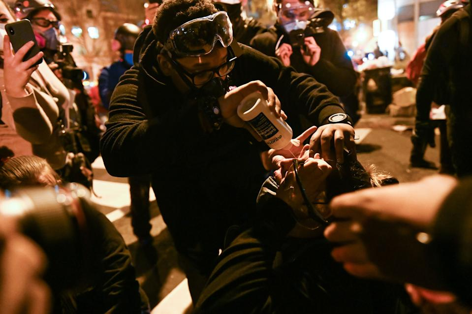 An anti-Trump demonstrator has her eyes rinsed after police used tear gas to push a crowd back near a local hotel in the vicinity of Black Lives Matter Plaza. Source: Getty