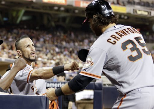 San Francisco Giants left fielder Andres Torres, left, greets teammate Brandon Crawford, right, after Crawford against the San Diego Padres off a single by Marco Scutaro during the seventh inning in a baseball game Friday, July 12, 2013, in San Diego. (AP Photo/Gregory Bull)