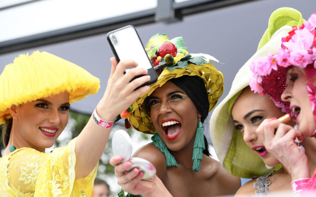 Spectators pose for a selfie before the running of the Melbourne Cup at the Flemington Racecourse in Melbourne, Australia, Tuesday, Nov. 6, 2018. (AP Photo/Andy Brownbill)