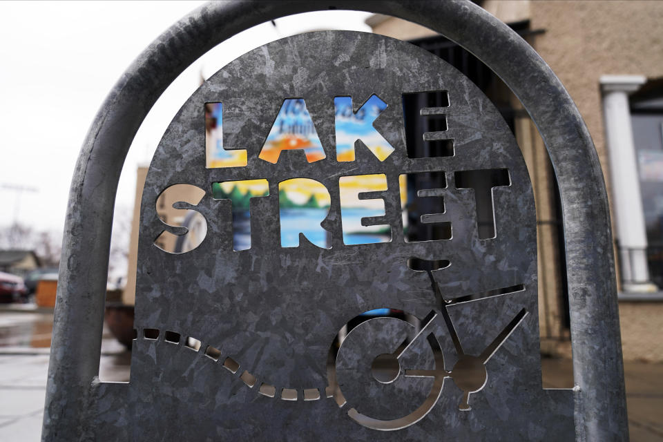 A store sign shows through a bicycle post bearing the name of Lake Street, March 24, 2021, in Minneapolis. Nearly a year after sometimes violent protests for racial justice shook Minneapolis, the immigrant corridor is struggling to recover. The street, which was the focus of much violence during the protests that followed George Floyd's death in police custody, has been a beacon for immigrants for more than a century. (AP Photo/Jim Mone)