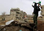 FILE PHOTO: A Syrian soldier, who has defected to join the Free Syrian Army, holds up his rifle and waves a Syrian independence flag in Saqba, in Damascus suburbs