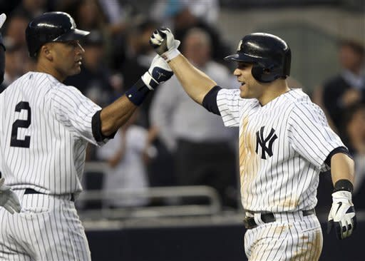 New York Yankees' Russell Martin, right, is greeted by teammate Derek Jeter after he hit a grand slam during the fourth inning of a baseball game against the Tampa Bay Rays at Yankee Stadium in New York, Tuesday, June 5, 2012. (AP Photo/Seth Wenig)