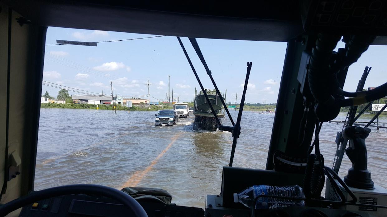 Light medium tactical vehicle's (LMTV) make their way through floodwaters near Bridge City in Texas.