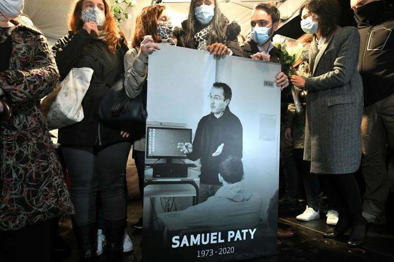 Relatives and colleagues hold a picture of Samuel Paty at a silent march in Conflans-Sainte-Honorine where he had worked as a history teacher before his murder