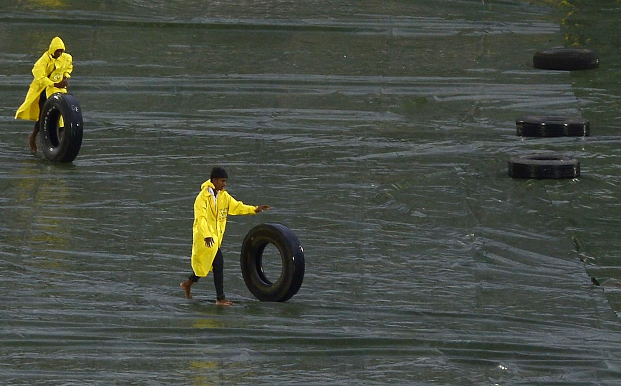 Sri Lankan ground staff roll out tyres to hold down tarps as rain stops play during the second One Day International (ODI) cricket match between Sri Lanka and New Zealand at the Suriyawewa Mahinda Rajapakse International Cricket Stadium in the southern district of Hambantota on November 12, 2013. AFP PHOTO/ LAKRUWAN WANNIARACHCHI        (Photo credit should read LAKRUWAN WANNIARACHCHI/AFP/Getty Images)