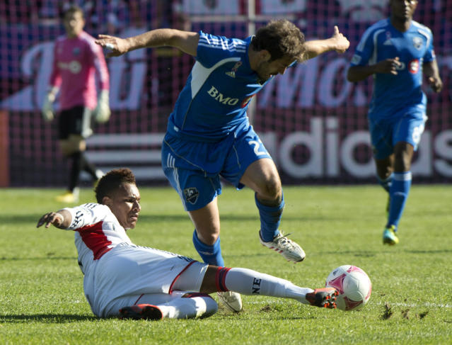 New England Revolution's Juan Agudelo, left, kicks the ball away from Montreal Impact's Hernan Bernardello during first half of an MLS soccer match on Saturday, Oct. 12, 2013 in Montreal. (AP Photo/The Canadian Press, Paul Chiasson)