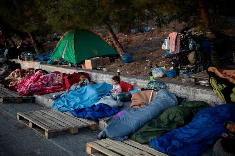 FILE PHOTO: Two children eat cookies as refugees and migrants from the destroyed Moria camp sleep on the side of a road, on the island of Lesbos
