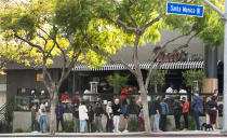 People wait in line for an open terrace table at a restaurant on Valentine's Day during the coronavirus pandemic, Sunday, Feb. 14, 2021, in West Hollywood, Calif. (AP Photo/Damian Dovarganes)
