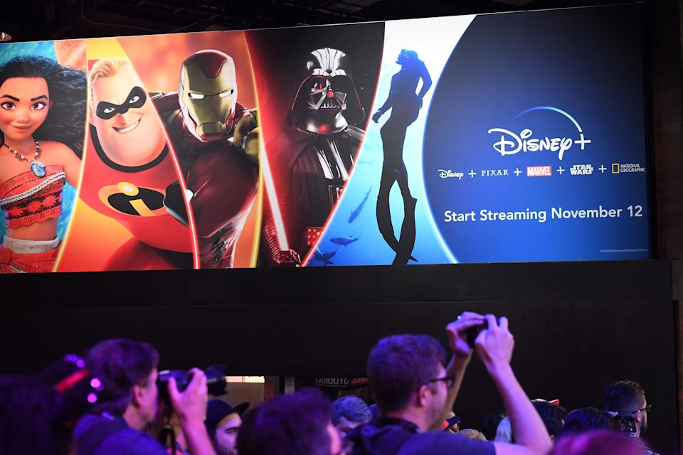 Attendees visit the Disney+ streaming service booth at the D23 Expo on August 23, 2019. (Credit: Robyn Beck/AFP via Getty Images)