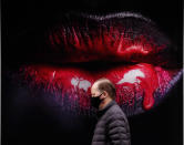 <p>A man wearing a face covering due to the COVID-19 pandemic walks past a poster in a shop in London, Wednesday, Feb. 17, 2021. (AP Photo/Frank Augstein)</p>