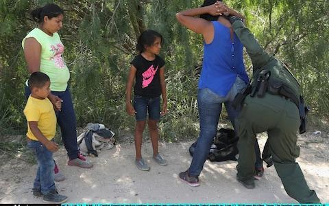 <span>Border crossers being taken into custody in Texas</span> <span>Credit: Getty </span>