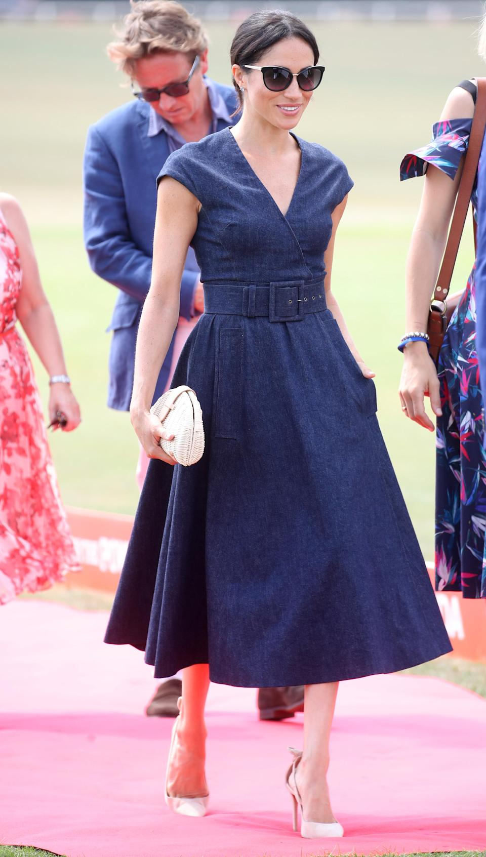 <p>Meghan looked chic in a £2,347 denim Carolina Herrera wrap midi dress with nude Aquazzura heels and a J.Crew rattan bag for the Sentebale Polo 2018 in July 2018 [Photo: Getty] </p>