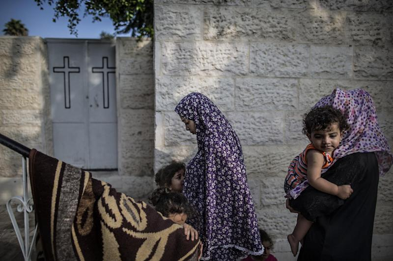 Displaced Palestinian women walk in the courtyard of a Greek Orthodox church where they are taking shelter in Gaza City, on July 23, 2014