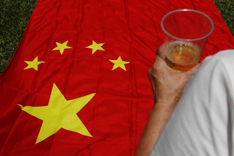 A pro-China supporter celebrates with champagne after China's parliament passes national security law for Hong Kong, in Hong Kong