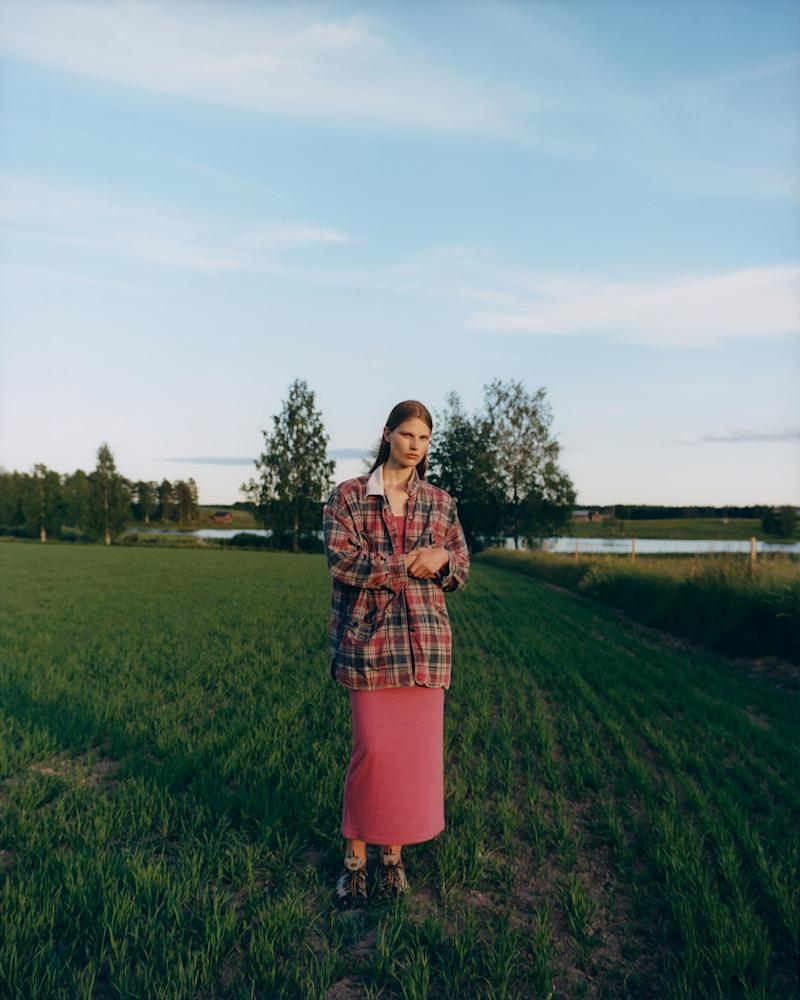 Adela standing out in a crop field wearing a vintage Isabel Marant dress, grandpa's sneakers, and her mom's old jacket.