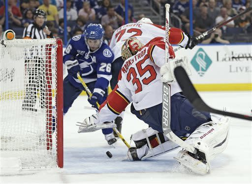Tampa Bay Lightning right wing Martin St. Louis (26) pushes the puck past Florida Panthers goalie Jacob Markstrom (35), of Sweden, for a goal during the second period of an NHL hockey game Saturday, April 27, 2013, in Tampa, Fla. (AP Photo/Chris O'Meara)