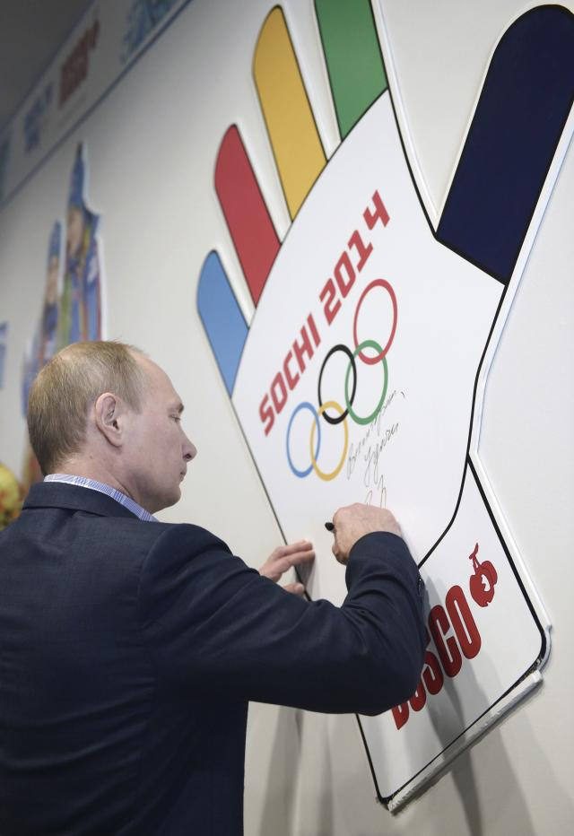 Russia's President Vladimir Putin signs a wall during his visit to an Olympic volunteer's centre in Sochi January 4, 2014. Putin has eased curbs on demonstrations in the Winter Olympics venue of Sochi in a gesture likely to burnish Russia's image ahead of an event dogged by security and human rights worries. REUTERS/Alexei Nikolskiy/RIA Novosti/Kremlin (RUSSIA - Tags: POLITICS SPORT OLYMPICS) ATTENTION EDITORS - THIS IMAGE HAS BEEN SUPPLIED BY A THIRD PARTY. IT IS DISTRIBUTED, EXACTLY AS RECEIVED BY REUTERS, AS A SERVICE TO CLIENTS