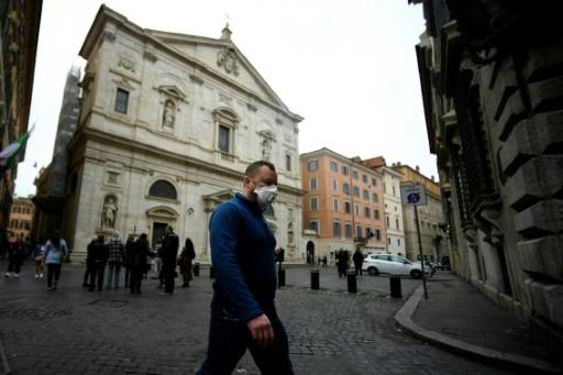 A man wearing a protective mask walks past the Church of St. Louis of the French (San Luigi dei Francesi) in Rome on March 1, 2020