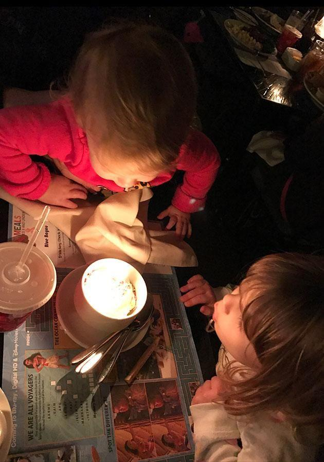 Jillian's daughters share a cupcake for their brother's birthday.