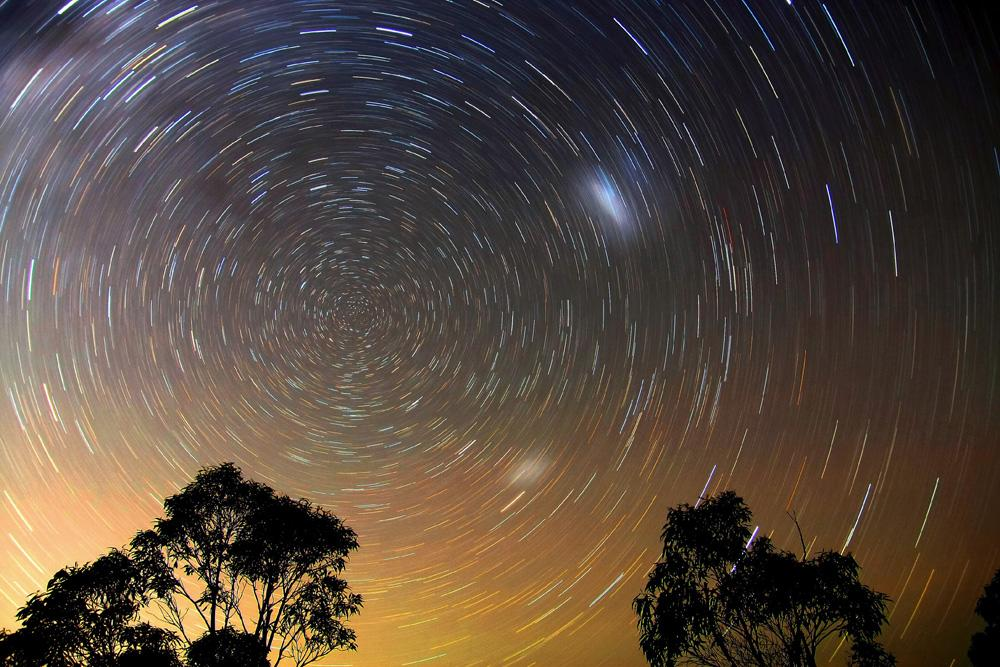 As the Earth rotates during the 30-minute exposure of this photograph the stars make trails around the sky's south pole. Taken in Australia, the Large and Small Magellanic Clouds, two neighbouring galaxies, appear as faint blurs in the sky. An equivalent photograph taken from Britain would show Polaris (the Pole Star) at the centre of the star trails. Ted Dobosz was the Winner of the 'Earth and Space' category, Astronomy Photographer of the Year, 2009 (Star Trails, Blue Mountains © Ted Dobosz, 2009)
