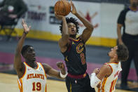 Cleveland Cavaliers' Collin Sexton (2) shoots against Atlanta Hawks' Tony Snell (19) and Trae Young (11) in the first half of an NBA basketball game, Tuesday, Feb. 23, 2021, in Cleveland. (AP Photo/Tony Dejak)