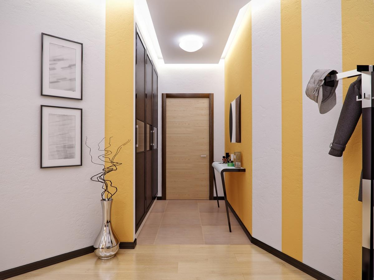 """Adding <a href=""""https://bestlifeonline.com/colors-that-make-rooms-feel-bigger/?utm_source=yahoo-news&utm_medium=feed&utm_campaign=yahoo-feed"""">some color to a small space</a>, like a hallway, can have a major impact—as long as it's the right one. <strong>Courtney Keene</strong>, director of operations for <a href=""""https://myroofingpal.com/"""" target=""""_blank"""">MyRoofingPal</a>, says choosing a lighter color paint for these areas will """"give the illusion of space."""" This way, the color won't overwhelm your home the way painting an entire room in a dramatic hue might."""