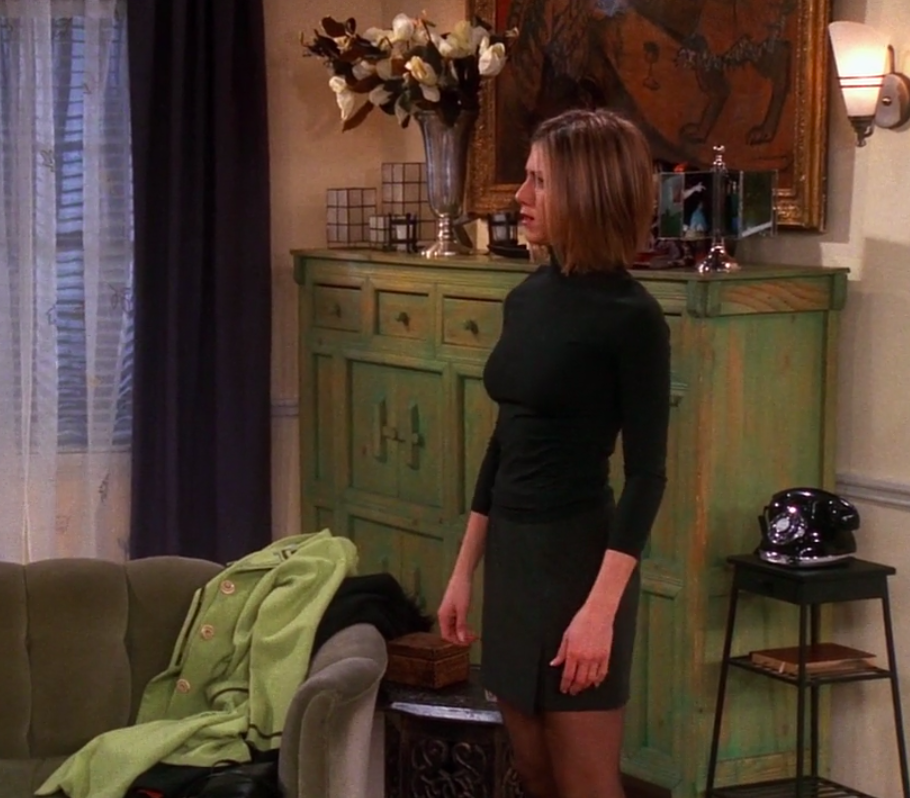 Rachel wearing boots, tights, a mini skirt, and a long-sleeve turtle neck