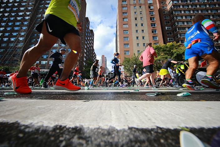 Runners step on used water cups discarded on the street during the 2019 New York City Marathon, Nov. 3, 2019. (Photo: Gordon Donovan/Yahoo News)