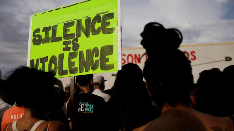 """At a rally after El Paso shooting on August 5, a sign is held aloft reading """"silence is violence."""""""