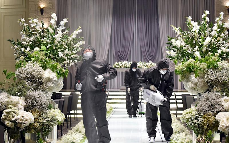 People wearing protective gear disinfect as a precaution against the new coronavirus at a wedding hall in Suwon, South Korea - Kim Jong-taik/NEWSIS