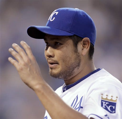 Kansas City Royals starting pitcher Bruce Chen waves to the crowd after coming out of the baseball game during the seventh inning against the Arizona Diamondbacks on Saturday, May 19, 2012, in Kansas City, Mo. (AP Photo/Charlie Riedel)