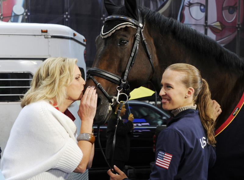 "This photo released by Good Morning America, Wednesday, Oct. 10, 2012, shows Ann Romney, wife of Republican presidential nominee Mitt Romney, left, planting a kiss on Lord Ludger while his rider Rebecca Hart watches on the set of the television show in New York. Romney said Wednesday that her love of horses helped her overcome her fear that multiple sclerosis would put her in a wheelchair. She was guest hosting ABC's ""Good Morning America"" when she spoke about her depression after receiving the diagnosis 14 years ago. Hart recently won the USEF National Para-Equestrian Championship. (AP Photo/ABC, Ida Mae Astute)"