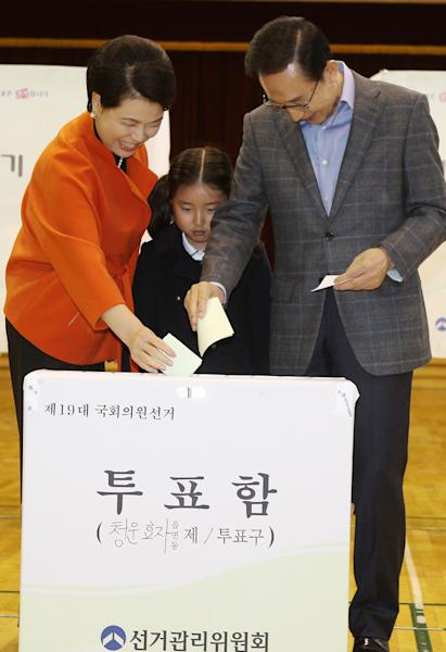 South Korean President Lee Myung-bak, right, and his wife Kim Yoon-ok cast their ballots in the parliamentary elections as their unidentified granddaughter looks on at a polling station in Seoul, South Korea, on Wednesday, April 11, 2012. (AP Photo/Kim Byung-man) KOREA OUT