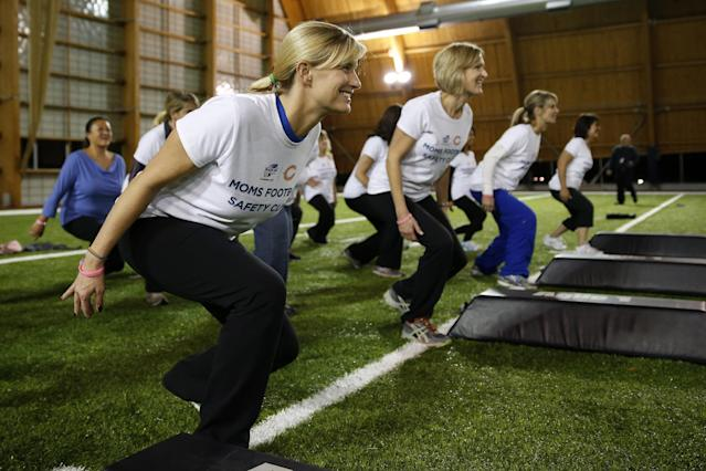 Participants including Cheryl Obenchain, left, of Chicago, receive instruction during a safety clinic hosted by the NFL and the Chicago Bears for the mothers of youth football players on Tuesday, Oct. 29, 2013, at Halas Hall in Lake Forest, Ill. (AP Photo/Andrew A. Nelles)