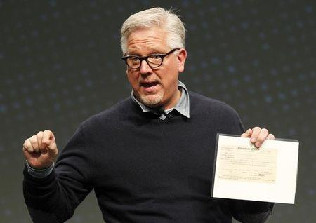 Radio and television personality Glenn Beck shows a copy of the Koran during a speech at FreePAC Kentucky in Louisville