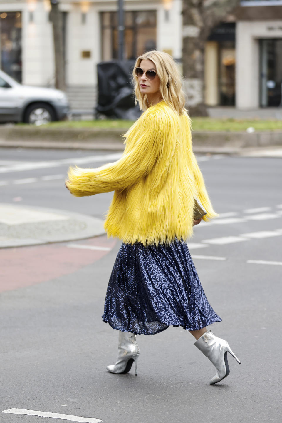 BERLIN, GERMANY - DECEMBER 14: German TV host Tanja Buelter wearing silver vintage ankle booties, a midi legth dark blue sequin skirt by Riani, a yellow faux fur jacket by Rene Lezard, sunglasses by Rodenstock and a silver clutch with snake pattern by Project Oona during a street style shooting on December 14, 2020 in Berlin, Germany. (Photo by Streetstyleshooters/Getty Images)