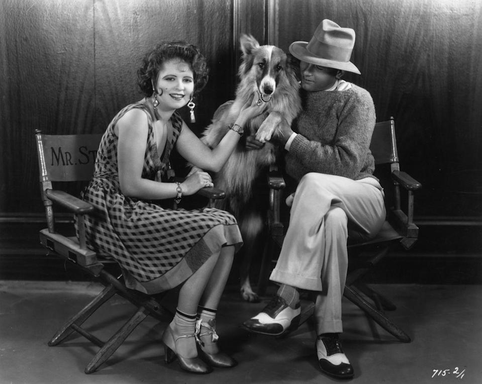 <p>Iconic 1920s film star Clara Bow is joined on the set of her film <em>The Fleet's In </em>by actor Richard Arlen and his dog, Scotty. </p>