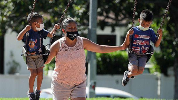 PHOTO: A woman and two children wear masks at a playground, July 11, 2020, in Los Angeles. (Marcio Jose Sanchez/AP, FILE)