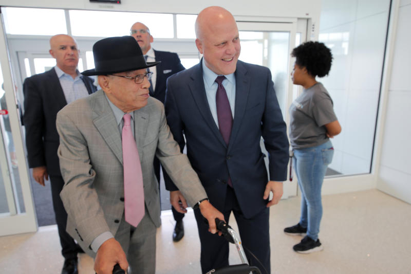 CORRECTS CITY TO KENNER, NOT BATON ROUGE- Former New Orleans Mayor Mitch Landrieu, right, greets Dr. Norman C. Francis, former President of Xavier University of Louisiana, as he arrives at a ribbon cutting ceremony for the opening the newly built main terminal of the Louis Armstrong New Orleans International Airport in Kenner, La., Tuesday, Nov. 5, 2019. (AP Photo/Gerald Herbert)