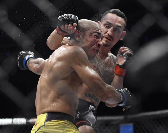 Max Holloway, right, punches Jose Aldo, of Brazil, during the third round of a UFC 218 featherweight mixed martial arts bout, early Sunday, Dec. 3, 2017, in Detroit. Holloway defeated Aldo by third-round TKO. (AP Photo/Jose Juarez)