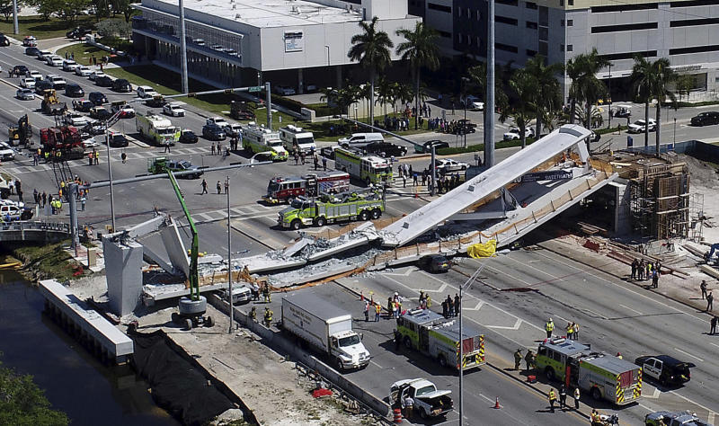 FILE - In this March 15, 2018, file photo, emergency personnel respond after a brand-new pedestrian bridge collapsed onto a highway at Florida International University in Miami. Federal officials have determined the Miami university bridge that collapsed and killed six people showed significant design errors and the state government should have conducted greater oversight because of the project's complexity. National Transportation Safety Board members concluded Tuesday, Oct. 22, 2019,  the design firm FIGG Bridge Engineers, Inc. underestimated the load of the bridge and overestimated its strength in a critical section that splintered, dropping a 174-foot-long (53-meter) span onto eight cars. (Pedro Portal/Miami Herald via AP, File)