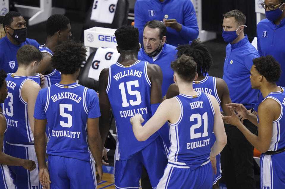 Duke head coach Mike Krzyzewski, top, talks to his team during the first half of an NCAA college basketball game against Louisville in the second round of the Atlantic Coast Conference tournament in Greensboro, N.C., Wednesday, March 10, 2021. Duke has pulled out of the Atlantic Coast Conference Tournament and ended its season after a positive coronavirus test and the resulting quarantining and contact tracing. The ACC announced that the Blue Devils quarterfinal game with Florida State scheduled for Thursday night has been canceled. (AP Photo/Gerry Broome)
